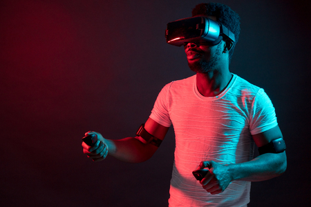 Foto de Young Man Wearing VR Headset And Experiencing Virtual Reality. Red blue dual color light on black background. - Imagen libre de derechos