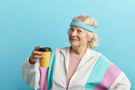 Mature female jogger in white sports suit taking a rest after morning running, holding cold drink in hands and looking at camera with cheerful look, isolated over blue background.
