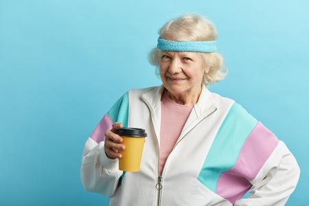 Positive cute grey haired mature woman wearing headband and white sports outfit, has coffee break, holds disposable cup of beverage, isolated on blue