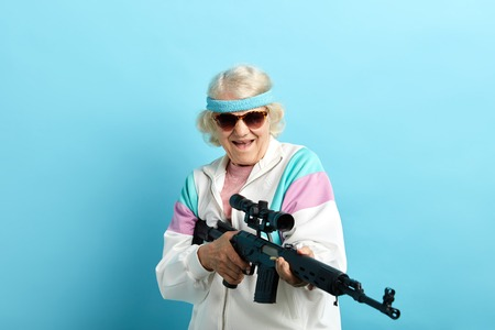 Photo pour Do not make your grandmother angry. Grandma can respond. Comic portrait of old-aged grandma in white sportive outfit and dark sunglasses holding sniper rifle, pointing aside over blue background - image libre de droit