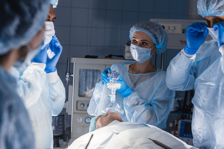 Photo pour Female nurses putting oxygen mask on patient in operation room. Jaw thrust maneuver technique for give oxygen and medication via mask from ventilator machine - image libre de droit