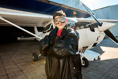 portrait of sweet little boy stands proudly in his fathers black leather pilot jacket, wears aviator glasses, looking with smile in camera, white propeller aircraft stands on the background.