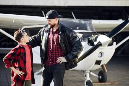 young father in black jacket and son in plaid shirt and jeans, stand smiling and looking at each other, feeling joyful after flight, happy to spend weekend together, light aircraft is parked behind.