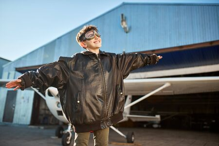 view of little boy standing with hands apart like wings outside hangar, in front of light propeller plane, dressed in large leather pilot jacket and aviator glasses, looking with smile in the sky.