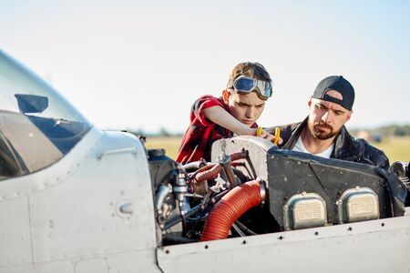 dad in black leather jacket and little son in aviator glasses doing together repair works at their private light propeller airplane at the airfield. Outdoor shot.