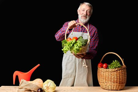 Friendly mature farmer shows results of hard work at his organic field and greenhouses, feels proud of rich havest, holds wicker basket with fresh raw vegetables. Studio shot, front view.