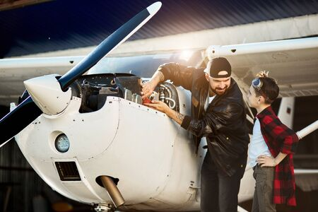 young dad and his lovely boy talking about their oncoming first flight together while repairing light propeller airplane engine, smiling and looking at each other, having great time and mood.