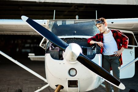 little boy stands outside hangar, near light single-engine airplane with screwdriver, looking at engine thoughtfully, dreams to be an aircraft engineer when he is adult.