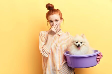 Photo pour ginger girl in gloves and stiped shirt touching her nose, she has found a stray dog and wants to wash it. closeup portrait. wellness and wellbeing of pets. cleanliness concept - image libre de droit