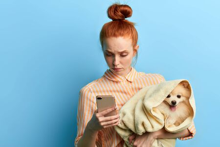 Foto de unhappy sad red-haired woman holding a towel with a dog and making a phone call, girl waiting for a vet, as her dog is ill. isolated blue background, studio shot.depression - Imagen libre de derechos