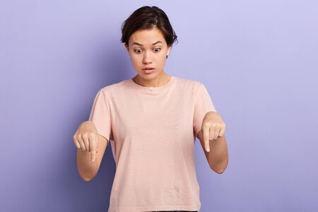 Foto de Beautiful emotional girl pointing down with fingers showing advertisement, woman with surprised face and open mouth looking down. close up portrait, isolated blue background, studio shot - Imagen libre de derechos