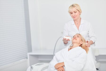 Photo for hardworking therapist lifting, cleansing the facial skin of patient at workplace. close up photo, copy space - Royalty Free Image