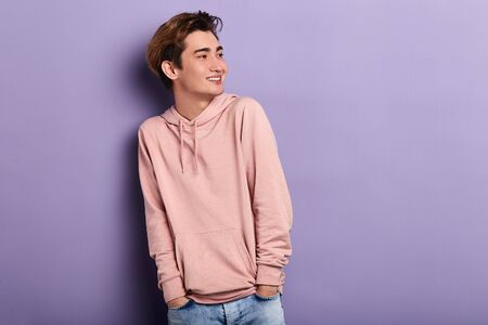 Foto de smiling cheerful man wearing pink hoodie, jeans looking aside, waiting for his friends. copy space. fashion, people, youth - Imagen libre de derechos