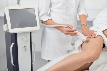 Foto de slim girl taking after her legs, new technology in medicine. close up cropped photo.healthy lifestyle - Imagen libre de derechos