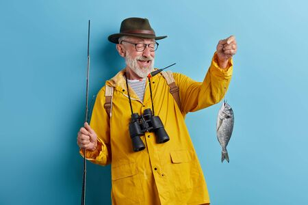 Photo pour smiling man in glasses with binocular wearing yellow raincoat and green hat raising his cought fiash, isolated blue background, stsudio shot - image libre de droit