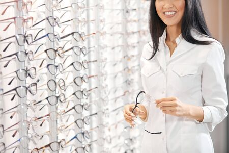 Foto de Asian woman in white medical uniform holding glasses, recommending customers to buy them. close up cropped photo - Imagen libre de derechos