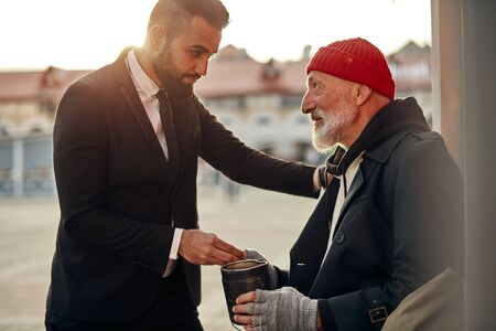 Photo for Man in tuxedo came up to beggar to help, give money donation. Rich man hold out his hand with money to homeless person. People relationship concepr - Royalty Free Image