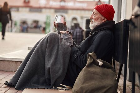 Photo for Beggar male sit with jar for money, wearing warm old clothes. Vagrant with grey beard, red hat and grey gloves freezing in the street - Royalty Free Image