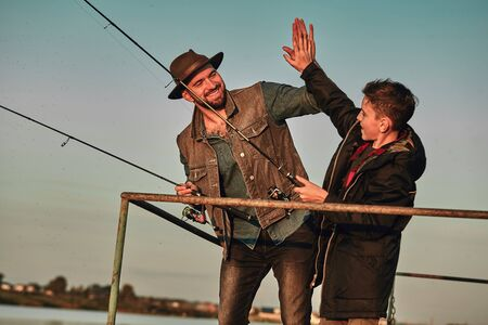 Photo pour Father and son stand on pier. They fish and give each other five - image libre de droit