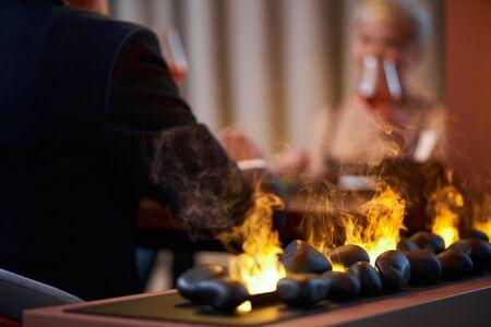 Photo pour Senior couple in dress and tuxedo raised wine near fireplace. Romantic evening for couple or love concept. Back view - image libre de droit