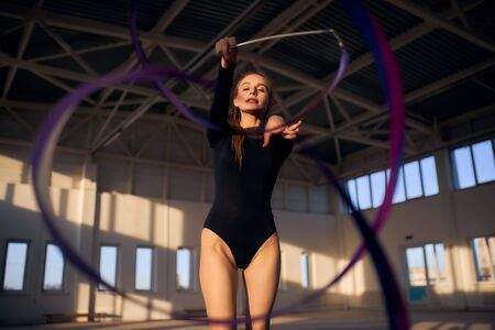 Photo pour portrait of young gymnasts training with colourful long ribbon in dark lighted sports hall, professional sport concept - image libre de droit