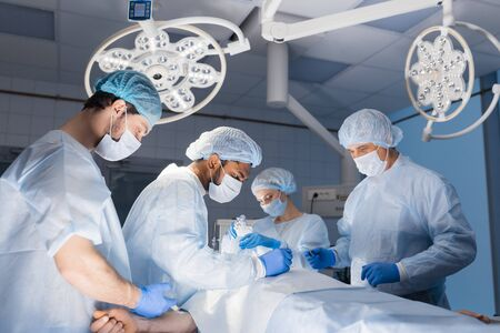 Photo pour Complex surgery. Skilful surgeon works with scalpels and clamps during an operation, and his asistants taking care of blood removal from the cut - image libre de droit