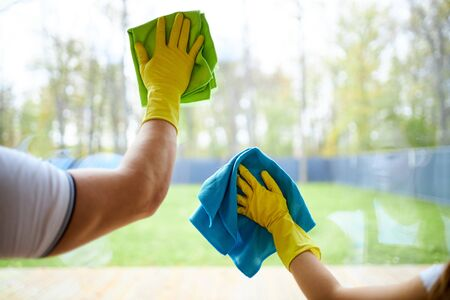 Photo for Closeup of cleaners holding rags, wearing yellow rubber gloves. Cleaning glass of window - Royalty Free Image