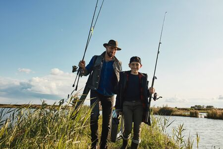 Photo pour Happy son go to fishing place, father follows. They hold fishing rods. Sunny warm day. - image libre de droit