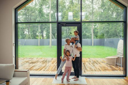 Photo pour Lovelt parents kissing. Beautiful and happy family together at home with panoramic window standing. Hug each other - image libre de droit
