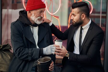 Photo for merciful businessman sit next to tramp in red hat and coat, rich man in black tuxedo. Vagrant get coffee from businessman - Royalty Free Image
