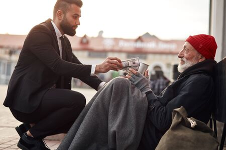 Photo for Kind man in suit hunkered down to homeless and give money donation, one dollar bill to beggar male - Royalty Free Image