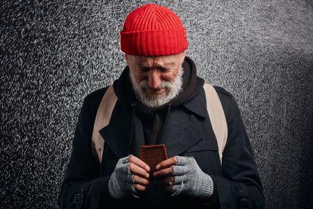 Foto de Bum cry about lack of food. Dream about shelter and food. Homeless man standing under rain - Imagen libre de derechos