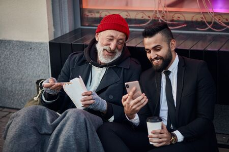 Photo for Man in tuxedo show interesting videos on phone to beggar male. Happy homeless man look, listen and smile - Royalty Free Image
