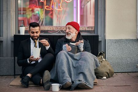 Photo for Stylish office worker and beggar male sit eating on street and speaking. Man un tuxedo, poor male in old clothes - Royalty Free Image