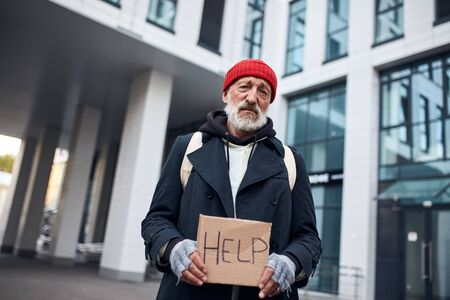 Photo for Poor man holding help sign made by cardboard, stand in the center of city, big beautiful business building behind him. - Royalty Free Image