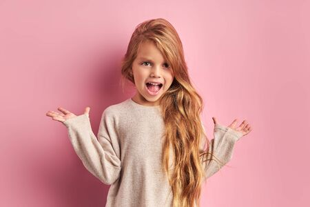 Foto de Portrait of charming joyful girl dressed in white blouse with opened mouth, with opened hands, shock or surprise. Posing at camera - Imagen libre de derechos