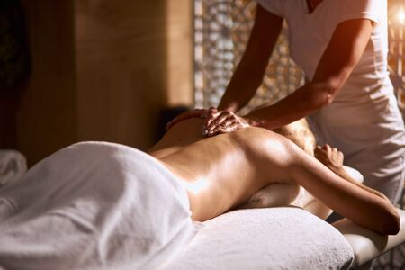 Photo for Professional female masseur doing deep shoulder massage in wellness beauty spa, woman lying on massage table under white towel, total relaxation concept, close up, indoor shot - Royalty Free Image