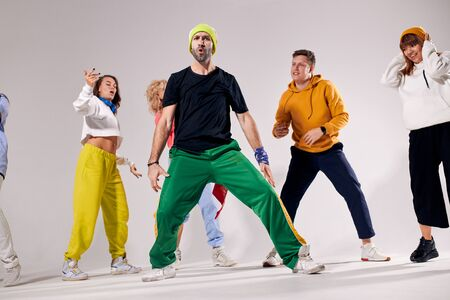 Handsome tall professional trainer teaching young teenagers how to dance breakdance, posing over white background, yelling loudly, looking away with opened mouth, energy dance, shot from below