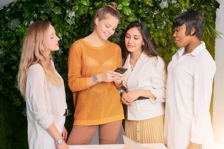 Photo pour attfour attractive diverse women gathered to discuss business ideas, use mobile phone during break time at work place - image libre de droit