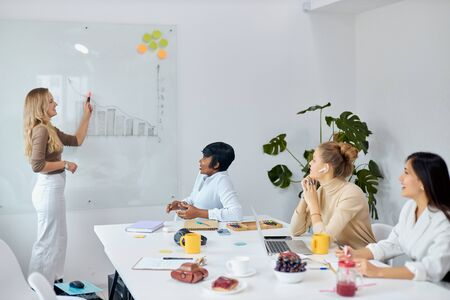 Photo pour Business people concept. young woman with blond hair give presentation to multi-ethnic group of people using flipchart - image libre de droit