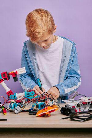Photo pour portrait of smart kid boy interestedly studying robots, assembling complex designs, look down at robots on table - image libre de droit