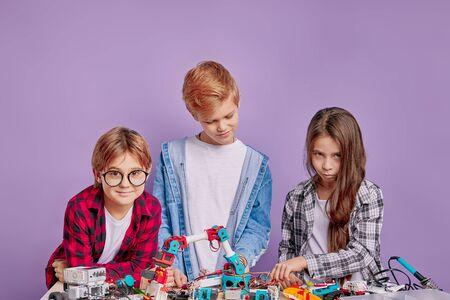 Photo pour portrait of clever children assembling robots on table, teamwork, children involved in engineering, robotics - image libre de droit