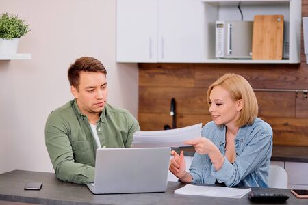 Photo pour couple checking analyzing utilities bills sitting together at kitchen table, husband and beautiful wife reading bank loan documents with laptop, family managing finances planning expenses together - image libre de droit