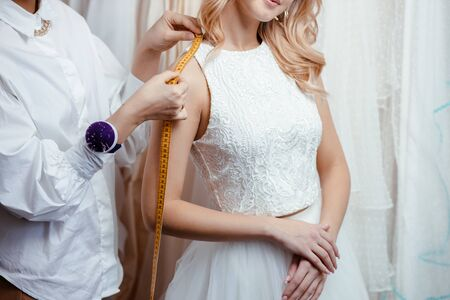 wedding concept. young tailor woman take measures of future bride, going to buy designers wedding dress. Sewing in salon