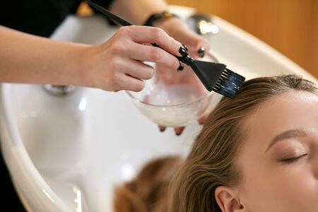 Photo for close up of young caucasian female hairdressed hands dyeing long hair to beautiful girl. Getting beauty procedures. - Royalty Free Image