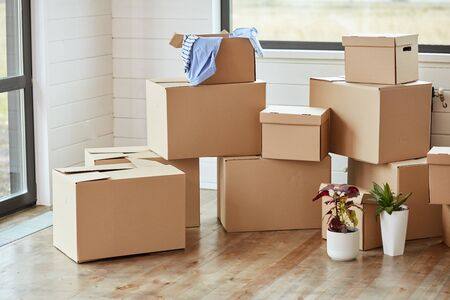 Photo for Twelve carton boxes with household stuff in light living room on moving day. Two flowers in pots on right side - Royalty Free Image