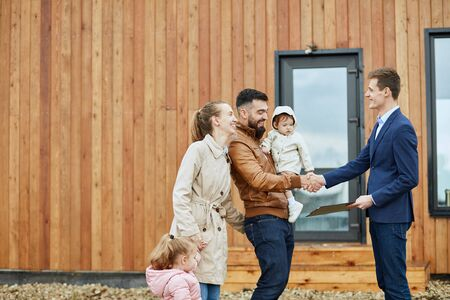 Photo pour Caucasian happy family of four and realtor wear blue suit stand outdoor near new house just sold. Men shake hands. - image libre de droit