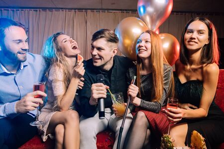 young women and men clubbers spend time in karaoke bar, have fun singing in microphone. leisure, celebration, party concept