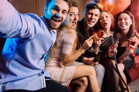 group of trendy young singers have fun together in karaoke bar, fashionable and positive guys and ladies celebrating, singing. positive pastime