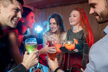 caucasian group of friends drink and have fun togeher in karaoke bar, beautiful girls and handsome guys chilling out and rocking together, have leisure time